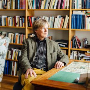 En äldre man vid en bokhylla.