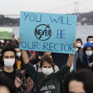 Bild på personer som demonstrerar. En kvinna håller upp en skylt där det står ''du kommer aldrig vara vår rektor''.