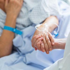 En hand med kateter håller i en sjukvårdares hand.