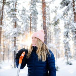 Nainen seisoo lumisessa metsässä nojaten lumilapioon.