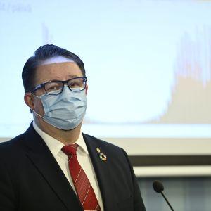 Institutet för hälsa och välfärds hälsosäkerhetschef Mika Salminen med munskydd på sig framför en mikrofon och en skärm med coronavirusläget.
