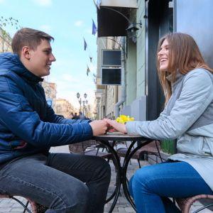 Ungt par sitter på uteservering och håller varandra i handen