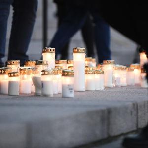 Ljus på riksdagshusets trappa. Ceremoni till minne av  den pojke som blev dödad av tre jämnåriga tonårspojkar i Helsingfors i december.