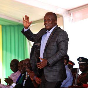 En äldre svart man i kostym står och vinkar med handen. Bakom honom sitter fler personer. John Magufuli inledde en ny presidentperiod i november 2020.