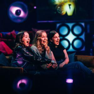Kolme nuorta naista istuu iloisesti nauraen sohvalla.