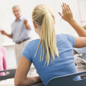 Skolelever sitter i ett klassrum och den manliga läraren står framför skrivtavlan.