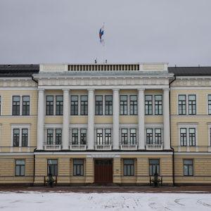 En byggnad i tre våningar och gul fasad med sex pelare. Reservofficersskolan i Fredrikshamn.
