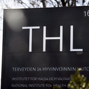 En svart skylt med texten THL och Institutet för hälsa och välfärd.