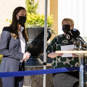 Sanna Marin och Annika Saarikko iförd munskydd, möter pressen utanför Ständerhuset.