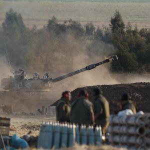 Bild på en tanker som står vid gränsen till Gaza. Bredvid står soldater från den israeliska militären IDF.