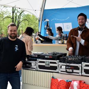 Två personer vid försäljningstält. Ena är DJ och pekar glatt på den andra.