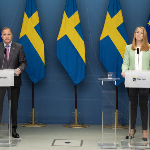 Stefan Löfven och Annie Lööf på pressträff med Sveriges och EU:s flaggor bakom sig.