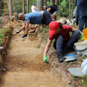 En grupp personer gräver i en grop i marken.