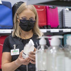 En kvinnlig butiksanställd med munskydd studerar en flaska med handdesinfektionsmedel.