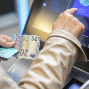 Veikkauksen rahapeli, kädet, raha ja veikkauskortti.