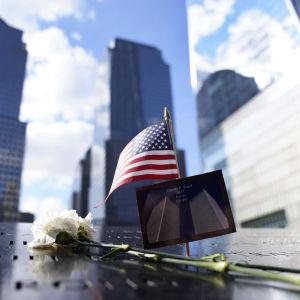 Bild på blomma och USA:s flagga mot minnesmärke vid Ground Zero.
