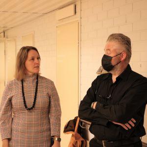 En man och en kvinna står och samtalar med varandra i en korridor.
