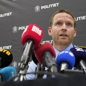 En polis sitter bakom en mängd mikrofoner.