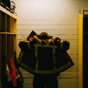 anonyymi henkilö pukee takkia päälle palolaitoksen pukuhuoneessa.