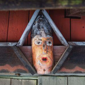 Puusta veistetyt kasvot räystääseen
