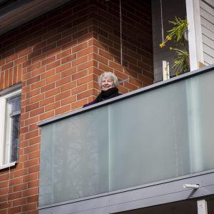 En äldre kvinna står på en balkong och tittar ut. Hon ler.