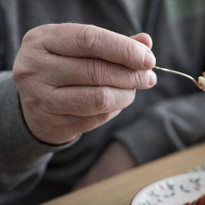 Eläkkeellä oleva mies syö kakkua.