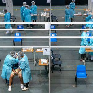 Joukko sinisiin suojapukuihin pukeutuneita lääkintätyönteklijöitä ottaa näytteitä isossa hallissa.