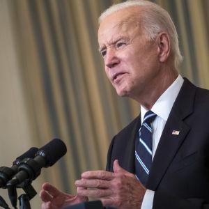 Yhdysvaltain presidentti Joe Biden puhuu mikrofoniin vakavana.