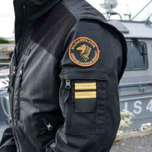 Anonym person i svart jacka. Gränsbevakningens emblem syns på axeln. En patrullbåt finns i bakgrunden.