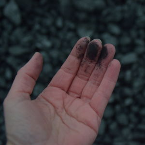 En hand med svarta fingrar av kolet antracit.