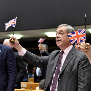 Nigel farage håller upp en brittisk flagga.