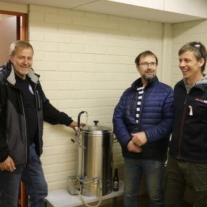 Tre män står vid en ölbryggartunna.