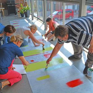 Flera personer målar en trasmatta på ett balkongsgolv
