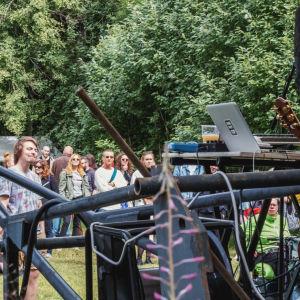 Ihmisiä seisovat nurmikolla kuuntelemassa bändiä, joka soittaa lavalla musiikkia.