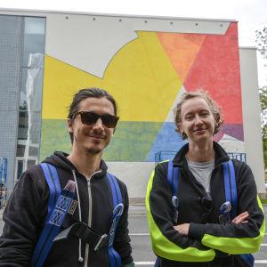 En kvinna och man med skyddskläder står framför påbörjad muralmåning.
