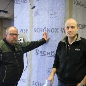 Två män står i ett duschutrymme som renoveras. Mannen till vänster står och lutar med ena handen mot en blå vägg.
