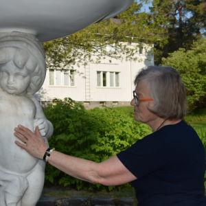 En äldre kvinna känner på en skulptur i vit marmor.