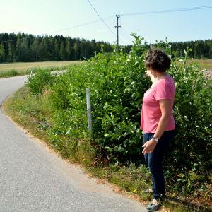 En kvinna står vid en vägkant och pekar ut på buskarna brevid vägen.