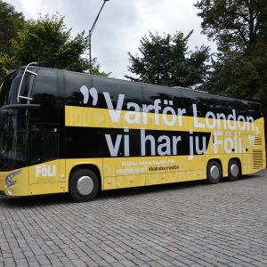 """Dubbeldäckarbussen är gul och över hela sidan står frasen """"Varför London, vi har ju Föli""""."""