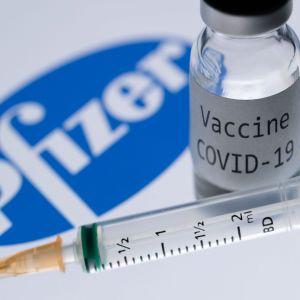 Bilden visar Pfizer-logon, en glasburk med covid-19-vaccin och en spruta.