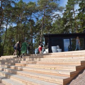 människor på trappor upp till hus i skog