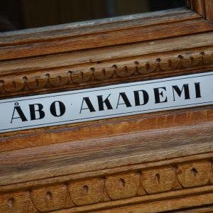 Gammal emaljerad skylt med texten Åbo Akademi, fäst på en dörr i ek.