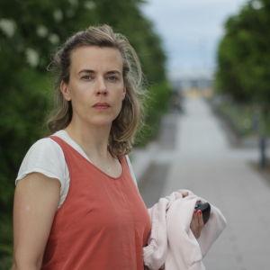 Vit kvinna med ljust hår står på en gångväg med gröna träd runt.