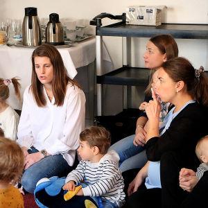 Föräldrar och barn sitter på golvet och sjunger.