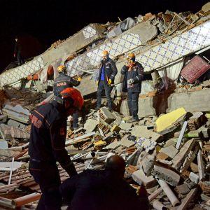Räddningspersonal i skyddshjälmar står vid ett förstört hus.