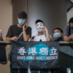 Viisi ihmistä kaiteen takana, osalla kasvoillaan suu-nenäsuoja, yhdellä naamari. Kaiteella kangas, jossa lukee Hong Kong Independence.