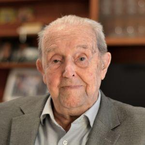 En äldre man som ser rakt in i kameran med ett litet leende.