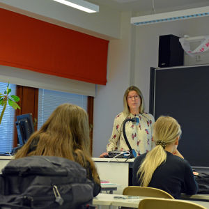 I bakgrunden en kvinna som föreläser i ett klassrum. I förgrunden sitter skolelever i sina skolbänkar.