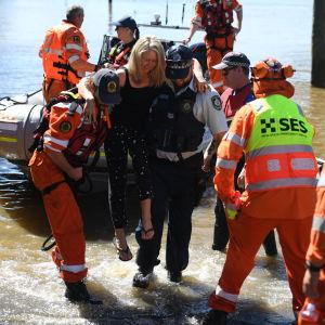 En kvinna som evakuerats undan Australiens översvämningar lyfts iland från en båt.
