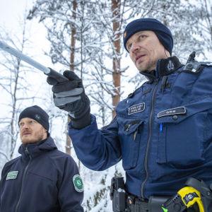 Susipartion jäsenet Tobias Peura ja Kimmo Örn etsii susien jälkie maastossa